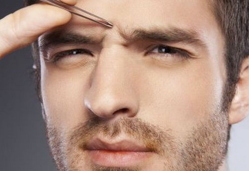 A man trying to get rid of unibrow using the plucking method.picture